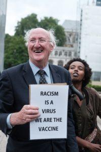 "Мужчина с плакатом, на плакате: ""Расизм - это вирус, мы - вакцина"""